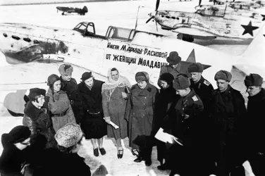 Делегация тружениц Молдовы передает летчикам построенный истребитель Як-7Б